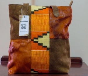 Orange-dyed Springbok fur with matching Kente and brown suede tote